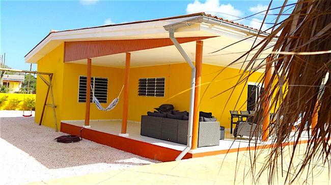 Op de schaduwrijke porch een bankstel en eettafels, zodat u heerlijk buiten kunt verblijven.