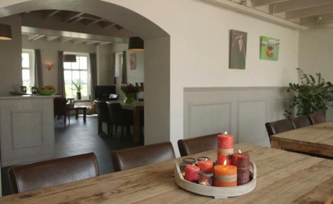Doorkijk van het eetgedeelte naar de woonkamer en keuken in De Hoeve Landgoed de Biestheuvel