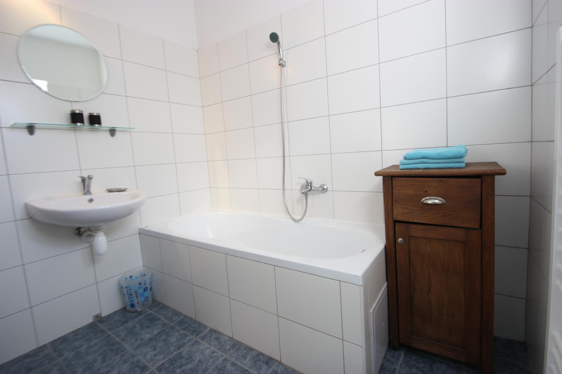 Badkamer met bad en separate douchehoek